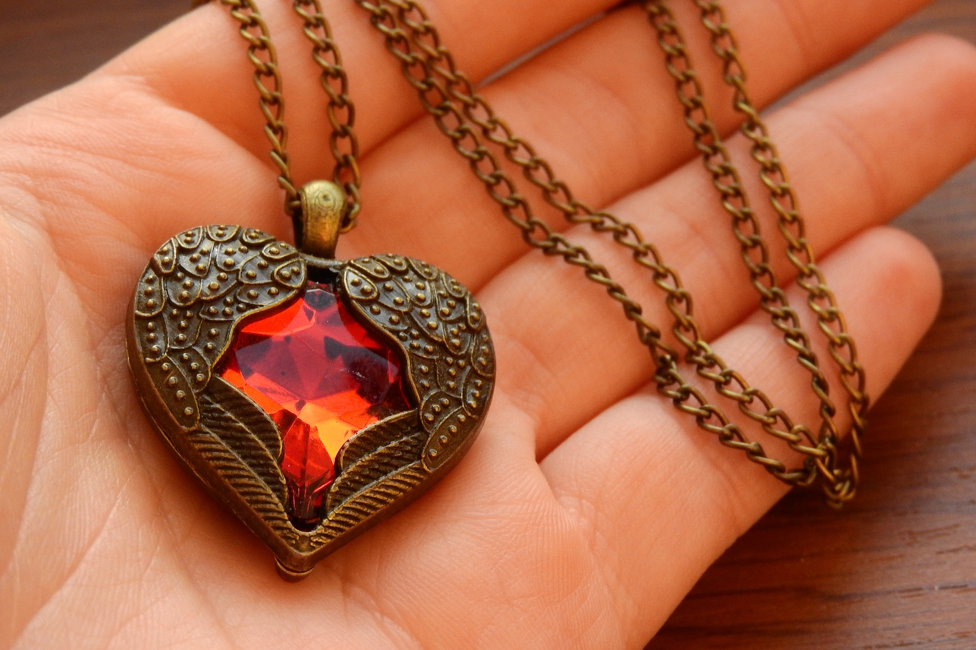 A heartshaped necklace with wings covering a red jewel 2