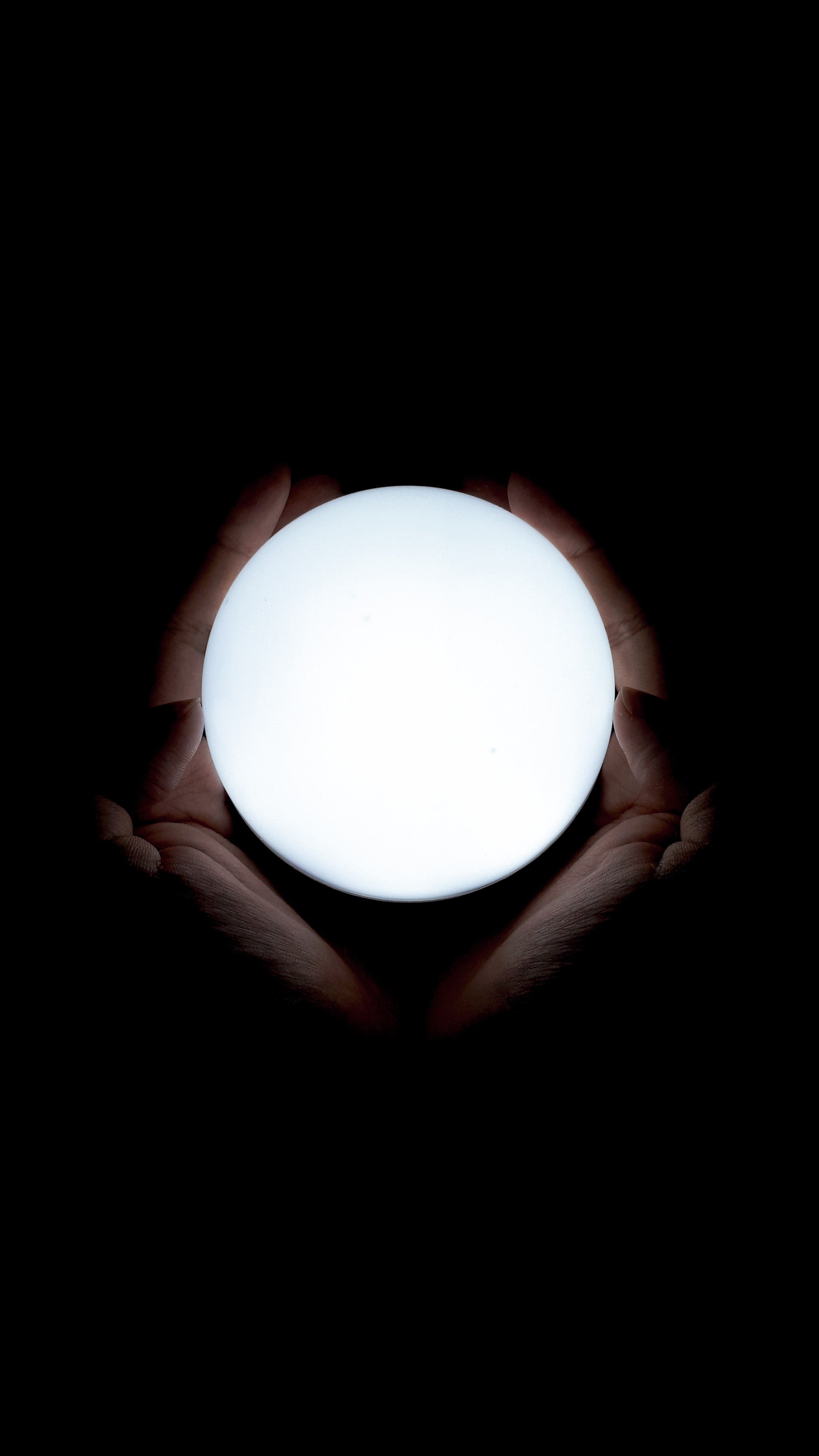A shining orb with a dark background and hands holding the orb
